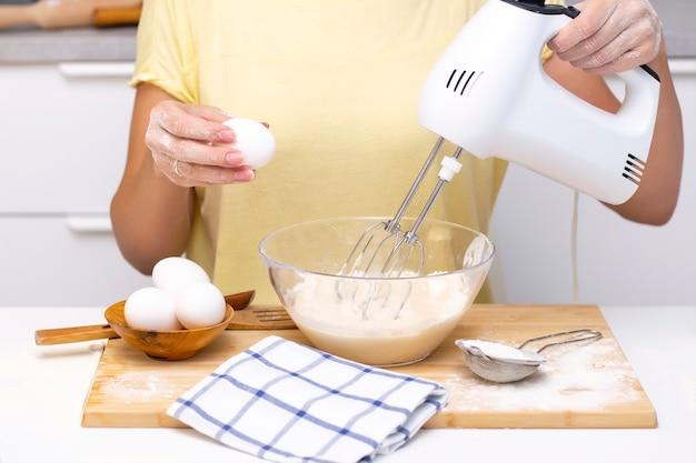 Prozess der herstellung von teig für pfannkuchen mit zutaten auf einem leuchttisch, eier und mehl werden mit einem mixer geschlagen