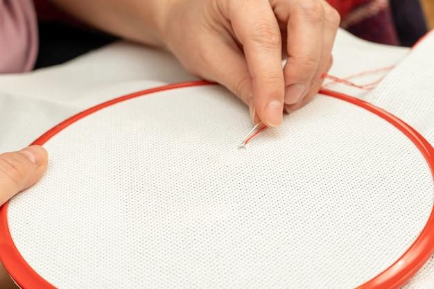 Prozess der kreuzstichstickerei auf stoff in einem rahmen mit händen