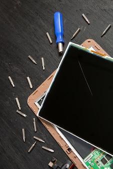 Prozess der reparatur des pc-tablet-geräts in der nähe von schraubenzieher und bit