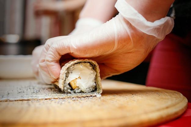 Prozess der sushi-herstellung, seltsame sushi-rolle mit mohn auf holzschreibtisch