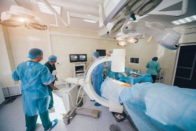Prozess der unfallchirurgie. gruppe von chirurgen im operationssaal mit chirurgischen röntgengeräten.