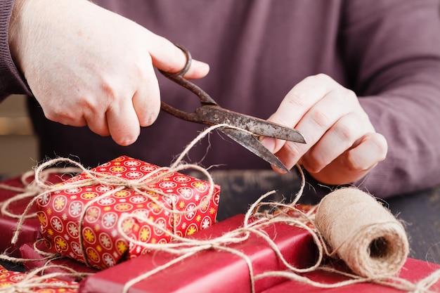 Prozess der verpackung und verpackung von weihnachts- und neujahrsgeschenkbox mit mannhänden