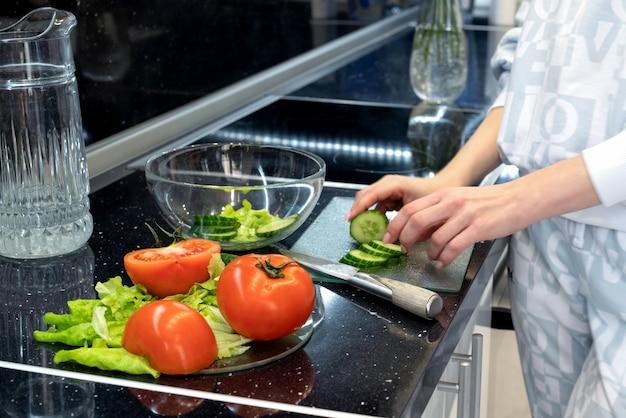 Prozess der zubereitung eines gemüsesalats. gurken und tomaten in scheiben schneiden. gesunde vegane ernährung und lebensweise