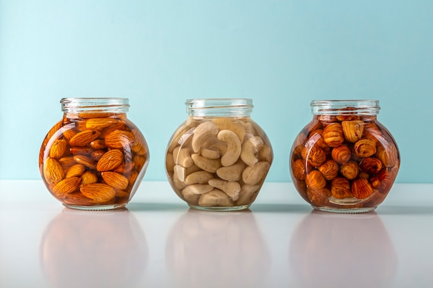 Prozess des einweichens verschiedener nüsse: mandeln, haselnüsse, cashewnüsse in wasser in einem glas zur aktivierung