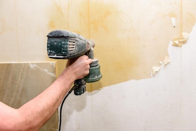 Prozess des entfernens alter tapeten. reinigung der wand von alten tapeten mit wasser.