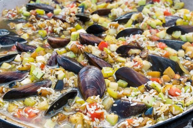 Prozess des kochens der paella mit meeresfrüchten