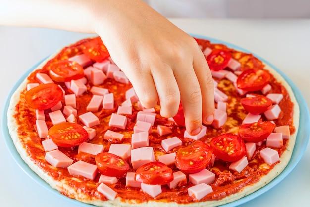 Prozess des kochens hausgemachter pizza durch kind.