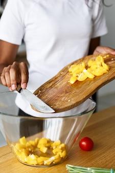 Prozess des kochens mit dem einsetzen des geschnittenen gelben pfeffers in die glaswaren