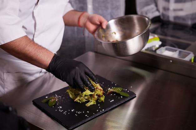 Prozess des kochens von warmem salat mit kalbfleisch. hände eines kochs in schwarzen handschuhen. schwarzes schieferbrett.