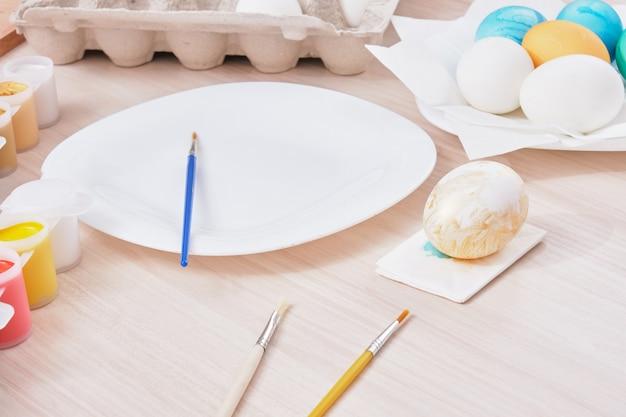 Prozess des malens von ostereiern, teller, pinseln und farben auf holztisch