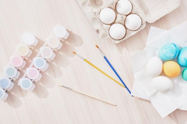 Prozess des malens von ostereiern, teller, pinseln und farben auf holztischoberansicht