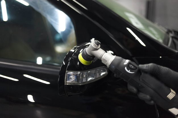 Prozess des polierens von autospiegeln mit einer poliermaschine und wachs. kratzer von einer karosserie entfernen
