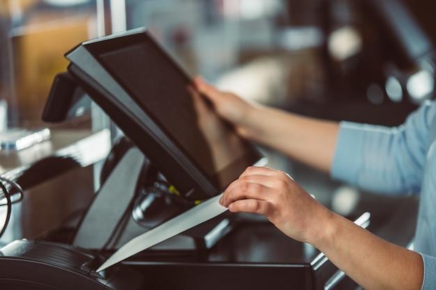 Prozess des rechnungsdrucks für einen kunden, kreditkartenprozessor, quittungsdrucker mit papiereinkaufsrechnung und touchscreen-monitor, pos
