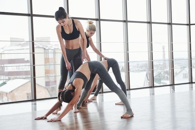 Prozess steuern. zwei ausbilder, die mädchen fitness-posen unterrichten, in der weißen großen turnhalle