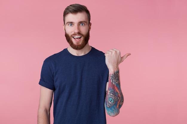 Prttrait des jungen glücklichen erstaunten rotbärtigen jungen kerls, mit dem weit geöffneten mund in der überraschung, der ein blaues t-shirt trägt und finger zeigt, um raum auf der rechten seite zu kopieren, isoliert über rosa hintergrund.