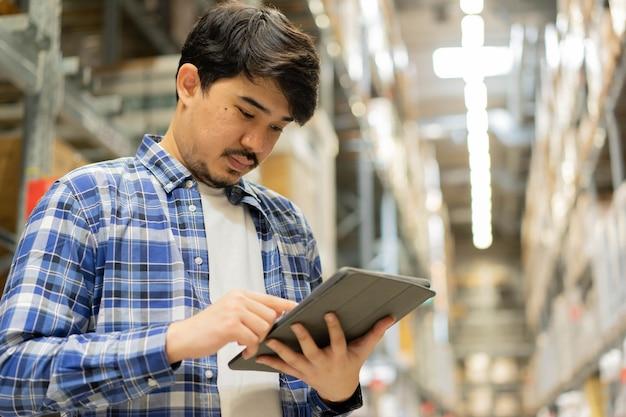 Prüfer aus dem nahen osten schauen und halten ein digitales tablet, um die bestellung im lager bei der verteilung zu überprüfen