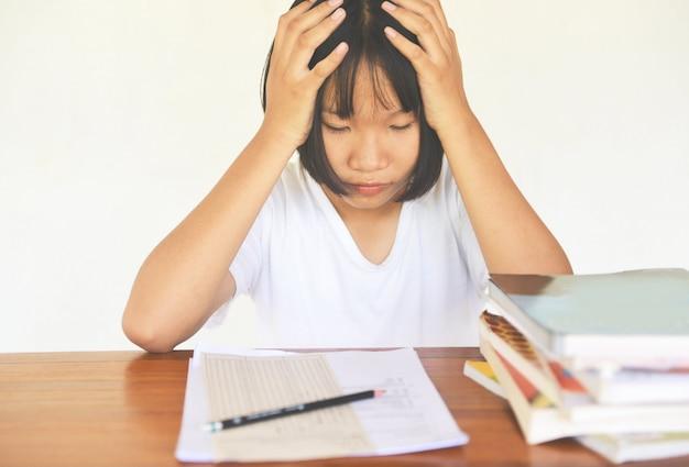 Prüfungsstress. ausbildung junge weibliche hochschule in der klasse, die kenntnisse nimmt und einen bleistift verwendet.