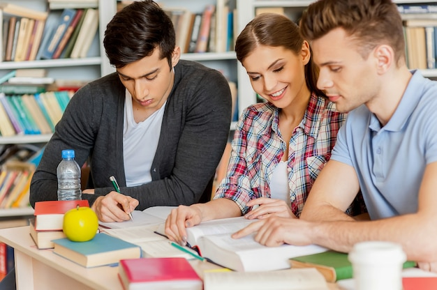 Prüfungsvorbereitung in der bibliothek. drei selbstbewusste studenten, die gemeinsam ein buch lesen, während sie am schreibtisch sitzen und gegen ein bücherregal in einer bibliothek