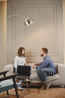Pschykologie und therapie. frau ist beim termin mit männlichem pschykologen. sitzen auf der couch im modernen schrank.