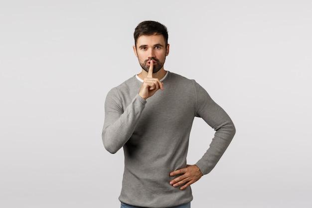 Pssst, sein geheimnis. sag es niemandem. geheimnisvoll charmanter und freundlicher junger bärtiger vater, der bittet, leise zu bleiben, mit dem zeigefinger an die lippen zu schweigen, den mund zu verschließen, zu erzählen, still zu sein
