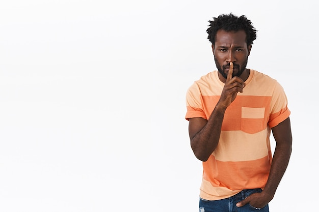 Pssst stille im unterricht. ernsthaft aussehender afroamerikanischer bärtiger typ in gestreiftem t-shirt fordert ruhe