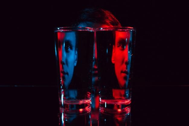 Psychedelisches porträt eines gutaussehenden mannes durch zwei gläser wasser mit roter und blauer neonbeleuchtung