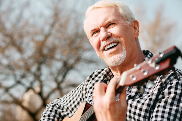 Psychische gesundheit. niedriger winkel des fröhlichen reifen mannes, der lacht und gitarrenspiel genießt