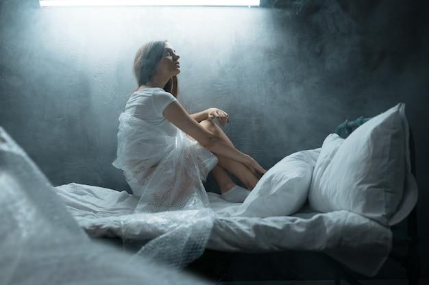 Psycho frau im verpackungsfilm sitzt im bett, schlaflosigkeit, dunkler raum. psychedelische weibliche person, die jede nacht probleme hat, depression und stress, traurigkeit, psychiatrie-krankenhaus