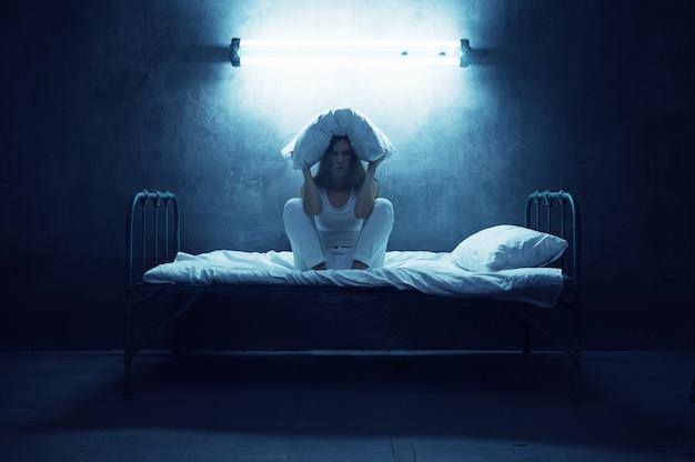 Psycho frau mit kissen über kopf sitzt im bett, dunkler raum. psychedelische person, die jede nacht probleme hat, depressionen und stress, traurigkeit, psychiatrische klinik