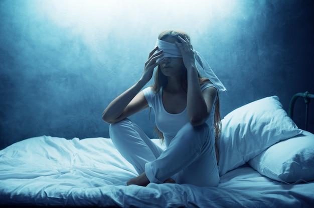 Psycho-frau mit verbundenen augen sitzt im bett, dunklem raum. psychedelische weibliche person, die jede nacht probleme hat, depression und stress, traurigkeit, psychiatrie-krankenhaus