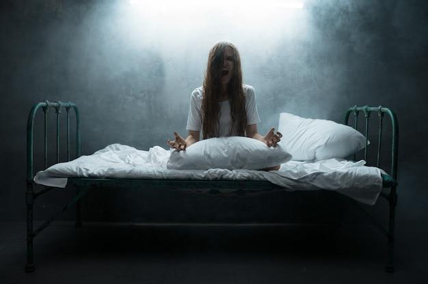 Psycho frau schreit im bett, schlaflosigkeit horror, dunkles rauchiges zimmer. psychedelische person, die jede nacht probleme hat, depressionen und stress, traurigkeit, psychiatrische klinik