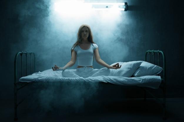 Psycho frau sitzt in yoga-pose im bett, dunklem raum. psychedelische person, die jede nacht probleme hat, depression und stress, traurigkeit, psychiatrie-krankenhaus