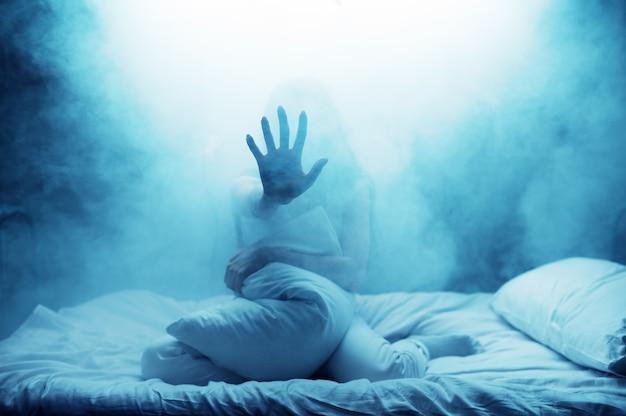 Psycho frau zeigen hand im bett, dunkles rauchiges zimmer. psychedelische person, die jede nacht probleme hat, depressionen und stress, traurigkeit, psychiatrische klinik