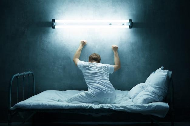 Psycho mann allein im bett, dunkler raum. psychedelische person, die jede nacht probleme hat, depressionen und stress, traurigkeit, psychiatrische klinik