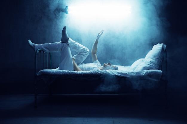 Psycho mann allein im bett, dunkles rauchiges zimmer. psychedelische person, die jede nacht probleme hat, depressionen und stress, traurigkeit, psychiatrische klinik