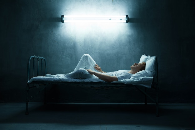 Psycho mann im bett liegend, dunkler raum. psychedelische person, die jede nacht probleme hat, depressionen und stress, traurigkeit, psychiatrische klinik