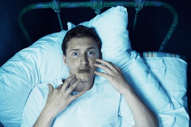 Psycho mann mit seinem mund genäht liegt im bett, schlaflosigkeit, dunklen raum .. psychedelische person, die jede nacht probleme hat, depressionen und stress, traurigkeit, psychiatrie krankenhaus