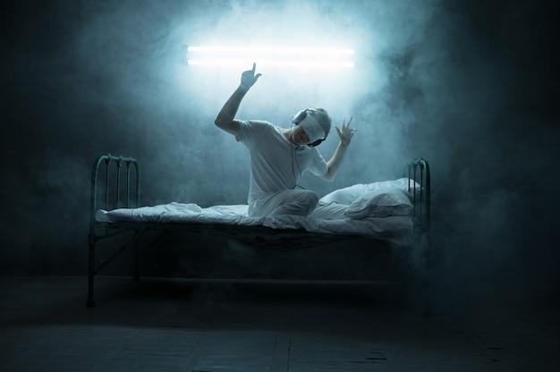 Psycho-mann mit verbundenen augen, der im bett sitzt, schlaflosigkeit-horror, dunkler raum. psychedelische männliche person, die jede nacht probleme hat, depression und stress, traurigkeit, psychiatrie-krankenhaus