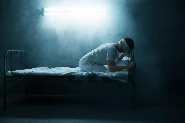 Psycho mann mit verbundenen augen sitzt im bett, schlaflosigkeit horror, dunkler raum .. psychedelische männliche person, die jede nacht probleme hat, depression und stress, traurigkeit