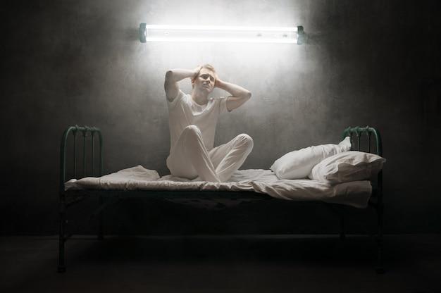 Psycho mann sitzt im bett, dunkles zimmer .. psychedelische person, die jede nacht probleme hat, depressionen und stress, traurigkeit, psychiatrie krankenhaus