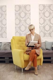Psychologe mit brille sitzt auf einem stuhl im büro