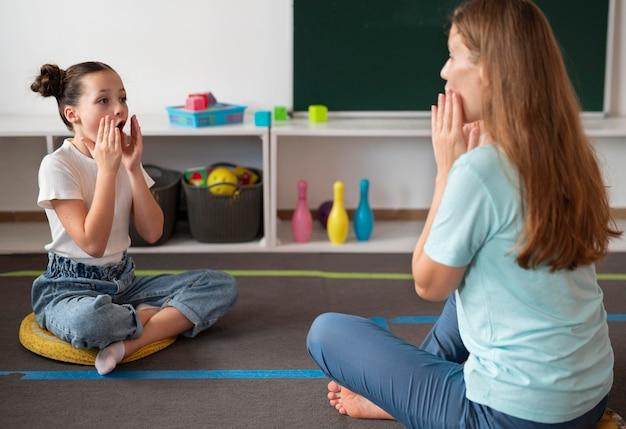 Psychologin, die einem mädchen in der sprachtherapie hilft
