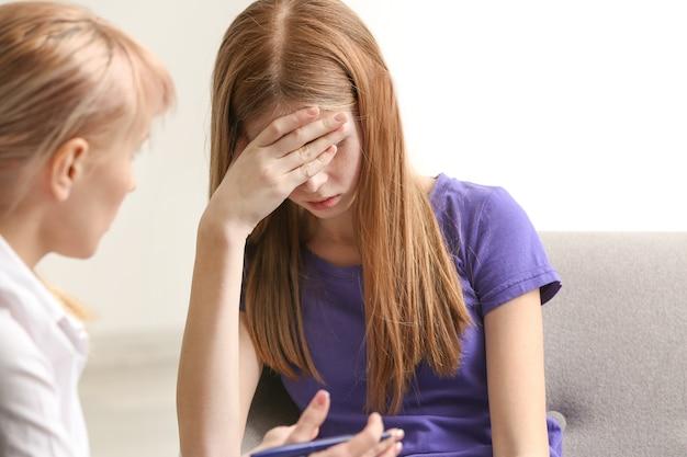 Psychologin, die mit trauriger teenagerin im büro arbeitet