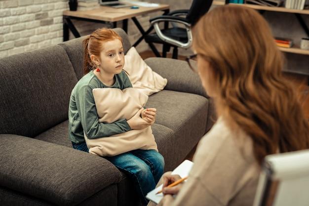 Psychologische probleme. trauriges, trostloses mädchen, das mit einem psychologen sitzt und sie um hilfe bittet