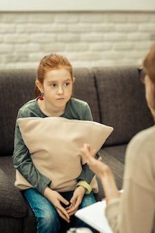 Psychologische therapie. nettes rothaariges mädchen, das mit einem kissen sitzt, während es eine psychologische sitzung hat