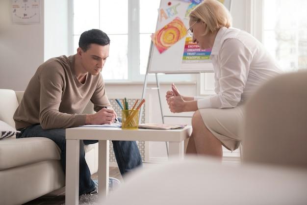 Psychologisches experiment. erfolgreicher reifer psychologe, der sitzung durchführt, während mann kunsttherapie versucht