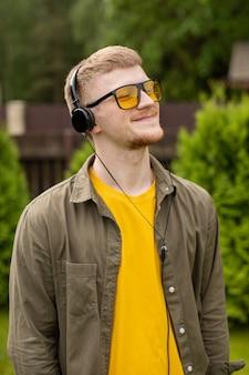 Psychologisches training, aufbau des selbstwertgefühls, motivierendes online-kurskonzept. seitenansicht-nahaufnahmeporträt des jungen mannes, der stereokopfhörer auf grünem hintergrund draußen hört.