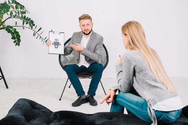 Psychotherapeut, der dem weiblichen patienten in der klinik rorschach testkarte zeigt