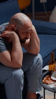 Psychotischer allein depressiver mann, der auf dem sofa sitzt und sich enttäuscht fühlt