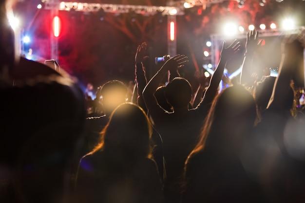 Publikum machen ein foto auf handy an einem freien nachtkonzert-musikfestival